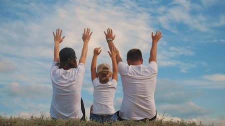 mavi : Family on grass with hands up and dream. Happy family concept, lifestyle, freedom.