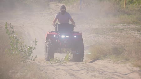 крайняя местности : Racing ATV on the sand in summertime. A young guy in sunglasses creates a large cloud of dust and debris on sunny day. ATV Rider in the action.