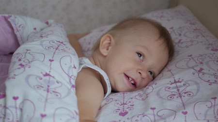 невинность : Little boy playing, falls asleep on bed before bedtime.