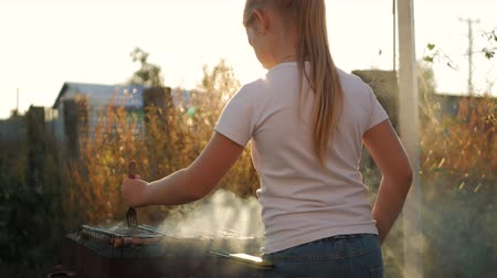 sosis : Little girl makes barbecue on the grill at green lawn.