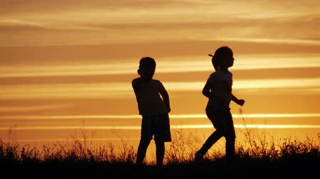 Two children dancing and enjoying nature on sunset. Childs silhouette. Happy childs have fun, enjoying nature.