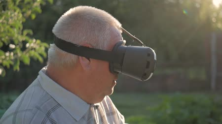 mobile game : Elderly Man Using Virtual Reality Headset Outdoor. Stock Footage