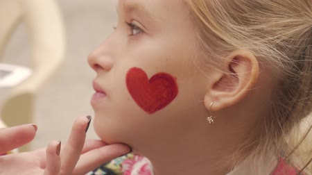 grim : Woman draws red heart on the child face with a brush. Aquarium. Stock Footage