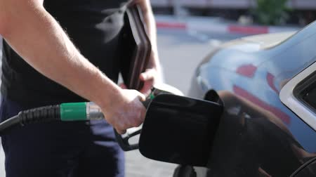 galão : Close up of petroleum gasoline station service - oil refueling and refilling for car transportation concept. Gas station, Fuel pump, Petrol pump filling nozzles.