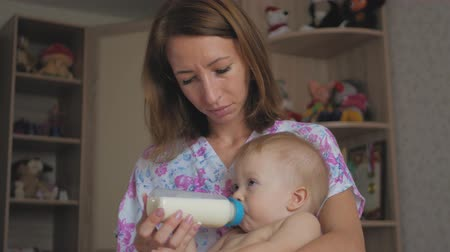 bottle feeding : Young mother feeding her baby son with a bottle of milk at home.