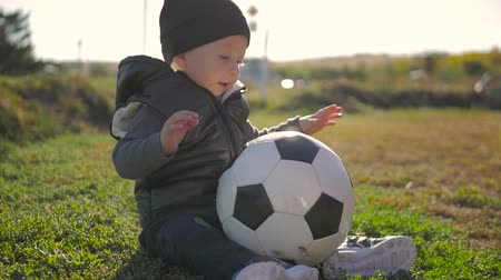soccer field : Smiling baby boy with a soccer ball at football field. Portrait of a little child sitting at stadium with a ball. Future football star. Football training concept.