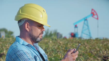 fossil fuel : Engineer oilman works with a mobile phone. Oil drill, field pump jack. Oil field, the oil workers are working. The Concept of Oil and Fuel Production.