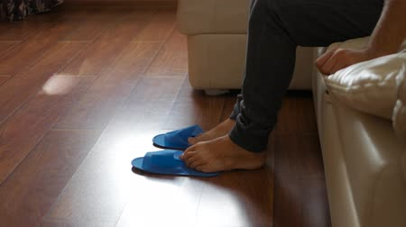 kap : A man gets up at bed and wears disposable slippers at hotel. Stock mozgókép