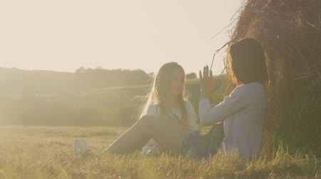 životní styl : Mom and daughter sit on the straw stack at sunset. Mother and her little daughter having good time in field outdoor. The concept of family and friendship.