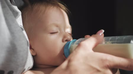 bottle feeding : Baby boy, asleep with bottle. Pretty baby boy drinking milk from bottle, close up. Stock Footage
