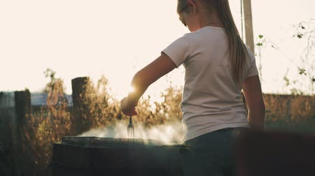 フランクフルター : Little girl makes barbecue on the grill at green lawn.