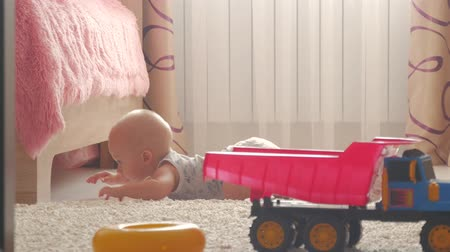 sitting floor : Childhood, kids and people concept - lovely baby boy playing with toys at home. Stock Footage