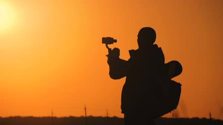 üretim : Silhouette man tourist hold stabilizer camera with a phone on the sunset background.