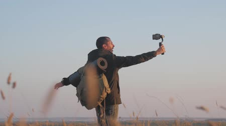 stabilizátor : The man tourist hold stabilizer camera with a phone on the sunset background. He takes a selfie and takes a video. Stock mozgókép