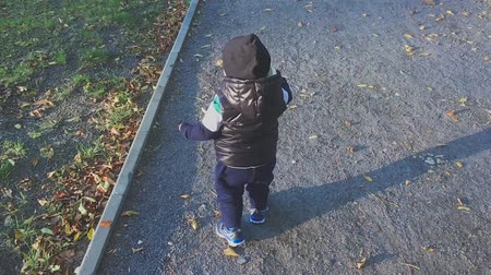 learning to walk : The one year old cute boy is making his first steps in the park. Child make his first steps outdoor. Slow motion video.