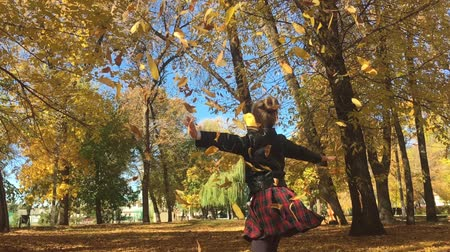 caído : Adorable happy school girl throwing the fallen leaves up, playing in the autumn forest. Beautiful girl having fun in autumn park. Slow motion. Vídeos