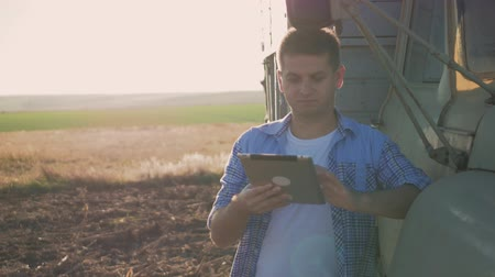 rolnik : A pensive farmer is working in the field. Uses a tablet, stands near the agricultural engineering.