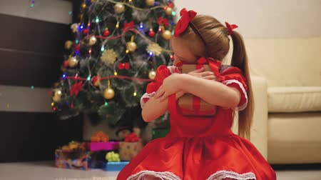 cozy : Child girl wearing a red dress opening Xmas presents. Happy little smiling girl with christmas gift box. Cozy warm winter day at home. Kid having fun at home. Xmas winter holiday concept. Stock Footage
