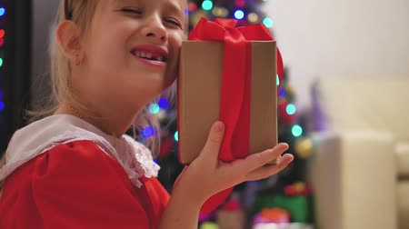 karácsonyi ajándék : Child girl wearing a red dress opening Xmas presents. Happy little smiling girl with christmas gift box. Cozy warm winter day at home. Kid having fun at home. Xmas winter holiday concept. Stock mozgókép