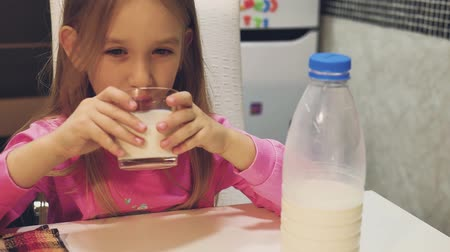 ailelerin : Child girl drinking milk at the kitchen at home.