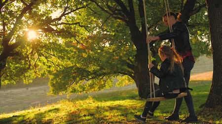 sun down : Happy young mom with a little girl swinging in the park together at sunset. Mother and daughter riding on swing, family having fun outdoor.