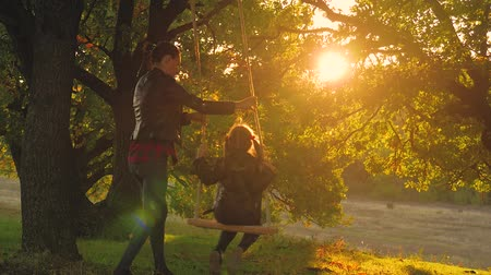 enjoyment : Young mother and her child daughter swinging on the swings and laughing a autumn warm evening outdoors. Happy loving family. Stock Footage