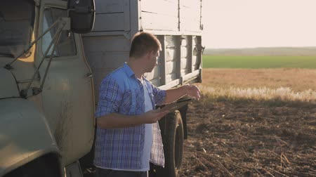 соя : A pensive farmer is working in the field. Uses a tablet, stands near the agricultural engineering.