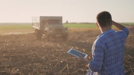 cereais : Handsome farmer with tablet standing with combine harvester in background. Farmer use modern technology touch tablet gathering data related to harvest sunflower. Concept the agro-industry.