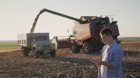 mezőgazdasági : Handsome farmer with tablet standing with combine harvester in background. Farmer use modern technology touch tablet gathering data related to harvest sunflower. Concept the agro-industry.