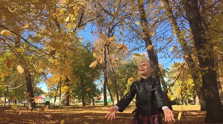 parky : Adorable happy school girl throwing the fallen leaves up, playing in the autumn forest. Beautiful girl having fun in autumn park. Slow motion. Dostupné videozáznamy