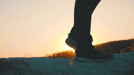 athletes foot : Hiker walking outdoors at sunset on the rock. Legs in trekking boots go along the mountain ridge against the backdrop of the sun Close up of leg walking in slow motion. Travel and adventure concept.