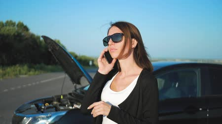 problem : Woman near a broken car on the road is calling for assistance. Young worried girl is using a phone to explain the mechanic the problem with a car that she has. Stock Footage