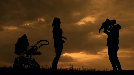 wozek dzieciecy : Silhouettes of happy parents having good time with their little baby boy on the outdoor at sunset. Silhouettes of parents walk with small child with a stroller.