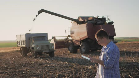 соя : Handsome farmer with tablet standing with combine harvester in background. Farmer use modern technology touch tablet gathering data related to harvest sunflower. Concept the agro-industry.