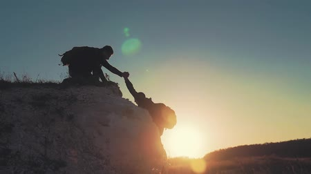 busqueda y rescate : Silhouette of helping hand between two climber. two hikers on top of the mountain, a man helps a man to climb a sheer stone. couple hiking help each other silhouette in mountains with sunlight.