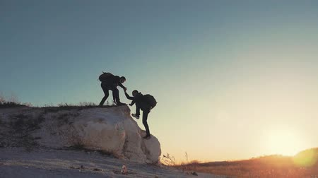 alpinista : Silhouette of helping hand between two climber. two hikers on top of the mountain, a man helps a man to climb a sheer stone. couple hiking help each other silhouette in mountains with sunlight.