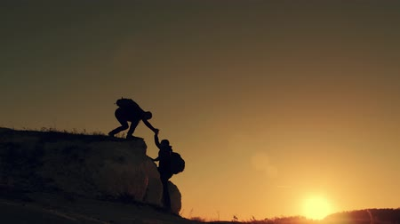 wspinaczka : Silhouette of helping hand between two climber. two hikers on top of the mountain, a man helps a man to climb a sheer stone. couple hiking help each other silhouette in mountains with sunlight.