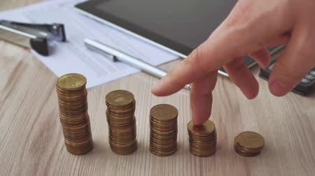 artış : Man hand holding coin dollar on money coin stack arranged as a graph on wooden table. Hand of male or female finger step coins stack growing growth saving money. Business idea.