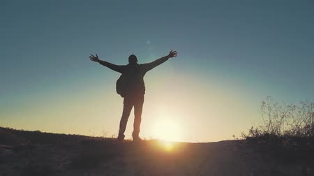wspinaczka : Silhouette of person in mountain. Young man with backpack standing with raised hands on top of a mountain. Sport and active life.