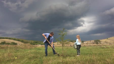 watering can : Father and daughter plant a tree seedling in a the garden. Friendly family.