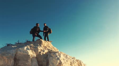 climber rock : Climber helping teammate climb, the man with the backpack reached out a helping hand to his friend. Hiker helping friend while trekking on hill. Tourist man helps someone to climb the mountain. Filmati Stock