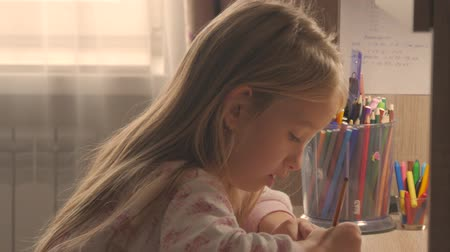 encouraging : Young girl makes its homework at on the table under the light of a lamp. Creative hobby of little princess. lifestyle of talented people.