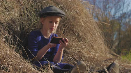 hay fields : Young cute girl with a cap having fun, sits in a haystack and use phone. Little girl sitting on hay. Stock Footage