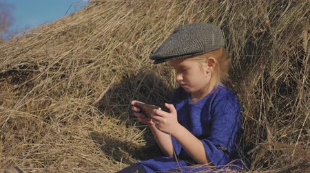 szénaboglya : Young cute girl with a cap having fun, sits in a haystack and use phone. Little girl sitting on hay. Stock mozgókép