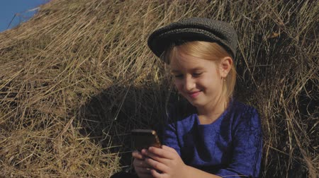 palheiro : Young cute girl with a cap having fun, sits in a haystack and use phone. Little girl sitting on hay. Stock Footage