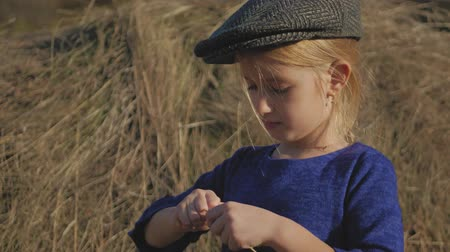 oturur : Young cute girl with a cap having fun, sits in a haystack and use phone. Little girl sitting on hay. Stok Video
