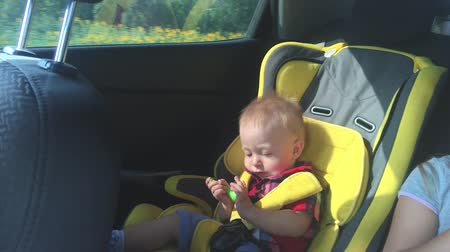 spona : A cute little baby sits in a car seat, a smile and a joy of travel. Dostupné videozáznamy