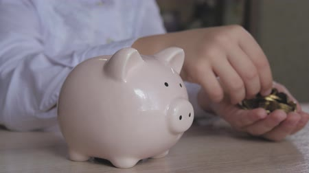 piggy bank : Happy girl save money in piggy bank in her home. Child inserting a coin into a piggy bank, indoor financial concept. Kid saving money for future concept. Stock Footage