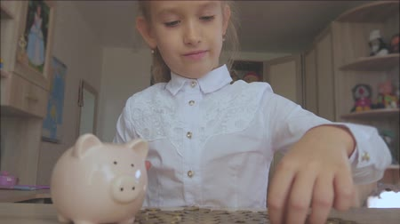 save the animals : Happy girl save money in piggy bank in her home. Child inserting a coin into a piggy bank, indoor financial concept. Kid saving money for future concept. Stock Footage