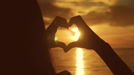 an : Young beautiful girl makes heart by her hands in heart shape framing setting sun at sunset over ocean. Emotional concept of happy exclusive lifestyle moment, sharing time, relaxing.